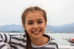 Chica joven sonriente que se sienta cerca por el mar en el puerto de Fethiye Imagenes de archivo