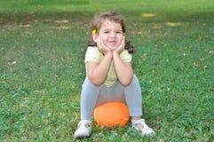Chica joven sonriente que se sienta en una bola Foto de archivo