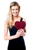 Chica joven sonriente que sostiene el regalo de la tarjeta del día de San Valentín Foto de archivo