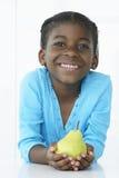 Chica joven sonriente que sostiene la pera fotos de archivo