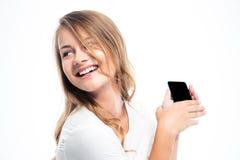 Chica joven sonriente que sostiene smartphone Fotografía de archivo