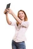 Chica joven sonriente que toma un selfie con su tableta Imagenes de archivo