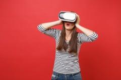 Chica joven sorprendente en la ropa rayada, vidrios de la realidad virtual que mantienen la boca abierta de par en par, poniendo  imágenes de archivo libres de regalías