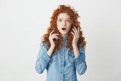 Chica joven sorprendida con el pelo rojo rizado que mira la cámara con los ojos abiertos sobre el fondo blanco Copie el espacio Fotos de archivo