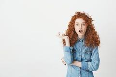 Chica joven sorprendida con el pelo rojo rizado que mira la cámara con los ojos abiertos sobre el fondo blanco Copie el espacio Imágenes de archivo libres de regalías