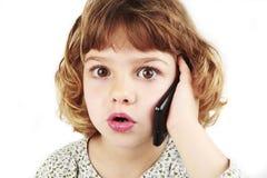 Chica joven sorprendida en el teléfono celular Imagenes de archivo