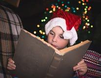 Chica joven sorprendida en un sombrero de la Navidad con un libro Imagen de archivo libre de regalías