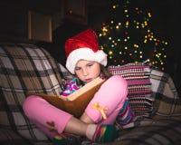 Chica joven sorprendida en un sombrero de la Navidad con un libro Imagenes de archivo
