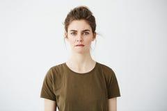 Chica joven tímida hermosa con el bollo del pelo que mira el labio penetrante de pensamiento de la cámara sobre el fondo blanco Imagen de archivo