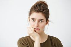 Chica joven tímida hermosa con el bollo del pelo que mira el labio penetrante de pensamiento de la cámara sobre el fondo blanco Fotografía de archivo libre de regalías