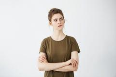 Chica joven tímida hermosa con el labio penetrante de pensamiento del bollo del pelo sobre el fondo blanco Brazos cruzados Foto de archivo libre de regalías