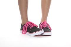 Chica joven tímida que presenta con los nuevos zapatos del cordón rosado Imagen de archivo