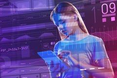 Chica joven tranquila que parece concentrada mientras que usa su dispositivo moderno Foto de archivo
