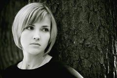 Chica joven triste cerca del árbol Imagen de archivo