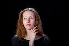 Chica joven triste con el pelo rubio que llora y que aumenta su mano derecha a su cuello Foto de archivo