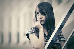 Chica joven triste contra una construcción de escuelas Imagenes de archivo