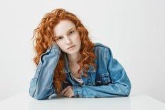 Chica joven triste descontentada con el pelo rizado del jengibre que mira la cámara que se sienta en la tabla sobre el fondo blan Fotos de archivo