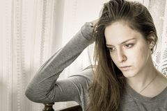 Chica joven triste en casa con una mano en su cabeza que mira lejos Imagen de archivo libre de regalías