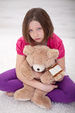 Chica joven triste que se sienta con el oso de peluche Fotografía de archivo