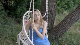 Chica joven triste que se sienta en un oscilación, suspiros y miradas en un punto Muchacha rubia en vestido azul en el oscilación almacen de video