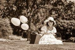 Chica joven triste y decepcionada que se sienta con su maleta sola Imagen de archivo libre de regalías