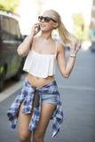 Chica joven urbana feliz que habla en el teléfono Fotos de archivo