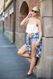 Chica joven urbana sonriente que habla en el teléfono Imagenes de archivo