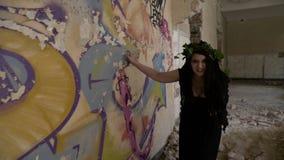 Chica joven vestida como bruja con la sonrisa sarcástica malvada que rasguña la pared de la mansión arruinada con los clavos almacen de video