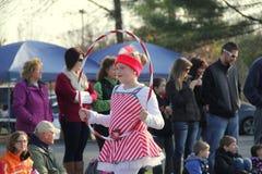 Chica joven vestida como un bastón de caramelo y ejecución con el aro en desfile de las vacaciones, Glens Falls, Nueva York, 2014 Fotografía de archivo libre de regalías