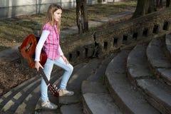 Chica joven vestida ocasional con la guitarra en su mano que camina encima de las escaleras en el parque Fotografía de archivo libre de regalías