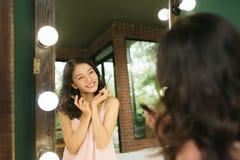 Chica joven vietnamita que aplica el rimel en espejo grande delantero imagen de archivo libre de regalías
