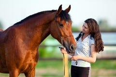 Chica joven y caballo de bahía al aire libre Imagen de archivo