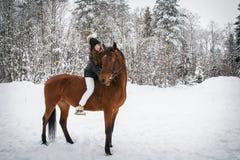 Chica joven y caballo en un bosque del invierno Foto de archivo
