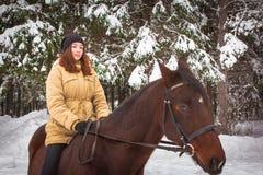 Chica joven y caballo en un bosque del invierno Imágenes de archivo libres de regalías