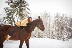 Chica joven y caballo en un bosque del invierno Imagen de archivo