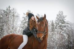 Chica joven y caballo en un bosque del invierno Fotografía de archivo