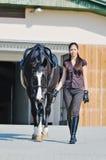 Chica joven y caballo negro Imágenes de archivo libres de regalías