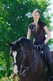 Chica joven y caballo negro Foto de archivo libre de regalías