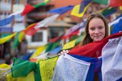 Chica joven y el volar budista de las banderas del rezo Viajes Foto de archivo
