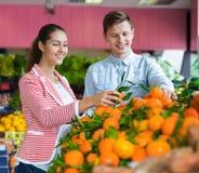 Chica joven y frutas cítricas de compra sonrientes del novio Imagen de archivo
