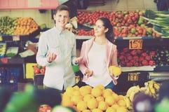 Chica joven y frutas cítricas de compra sonrientes del novio Fotos de archivo libres de regalías