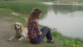 Chica joven y Labrador del pelirrojo en el lago metrajes