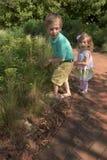 Chica joven y muchacho que caminan y que juegan en un jardín botánico Foto de archivo