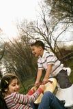 Chica joven y muchacho que juegan en el balancín Foto de archivo libre de regalías