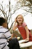 Chica joven y muchacho que juegan en patio Foto de archivo