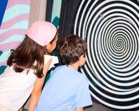 Chica joven y muchacho que miran el i óptico de giro imagen de archivo libre de regalías