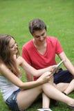 Chica joven y muchacho sonrientes que leen una tableta Imagen de archivo