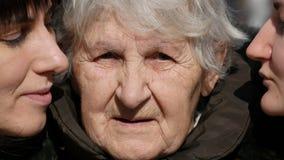 Chica joven y mujer adulta que besan a la abuela en mejillas, abuelita que sonríe y que mira a la cámara