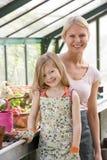Chica joven y mujer en la sonrisa del invernadero Imagen de archivo