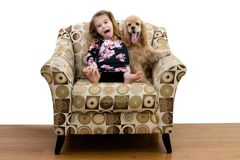 Chica joven y su perrito que se relajan en una butaca imagen de archivo